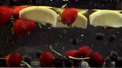 Lemons, cherries and berries soaked in transparent liquid
