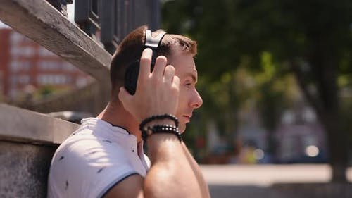 Man Puts on Big Headphones in a Park