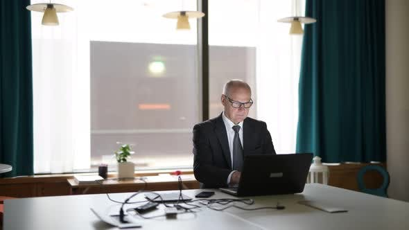 Cover Image for Senior Businessman Using Phone And Laptop In The Office