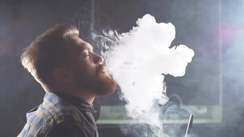 Handsome Guy Smoking Shisha in the Dark Room.