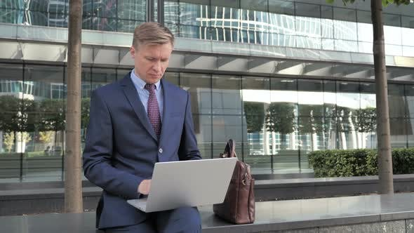 Thumbnail for Businessman working on Laptop Outside Office