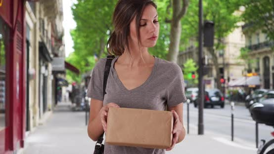 Woman reading address on parcel and walking off screen while out in city