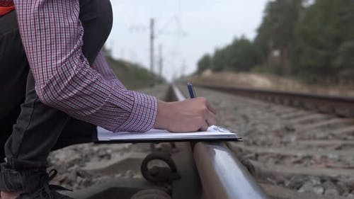 Railway engineer counts the number of sleepers and writes in a notebook.