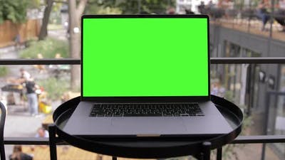 MacBook Pro Green Screen Laptop Standing on the Desk in the Modern Co-working park.