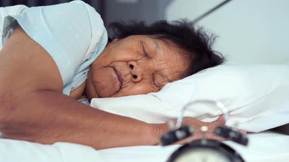 senior woman sleeping on a bed with a clock