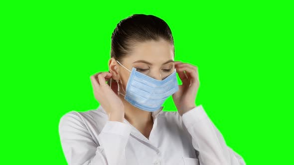Thumbnail for Young Doctor Putting on Health Mask. Green Screen. Closeup