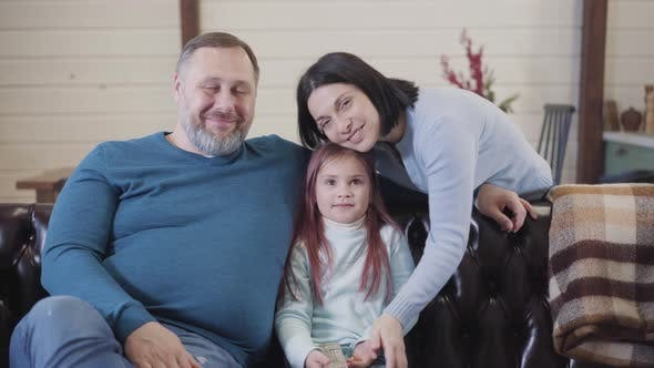 Thumbnail for Happy Family Posing in Living Room at Home. Portrait of Smiling Caucasian Father, Mother and