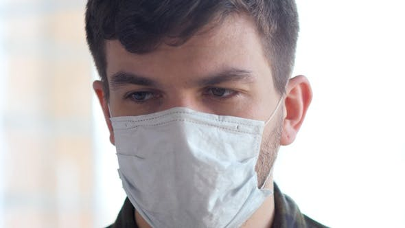 Thumbnail for Young man with medical flu mask on afraid of epidemic COVID-19.