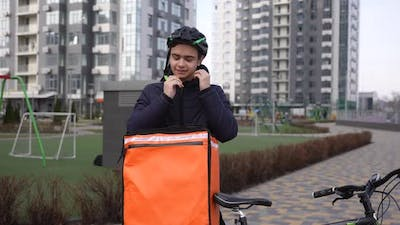 Tired Delivery Man Taking Off Bike Helmet Outdoors