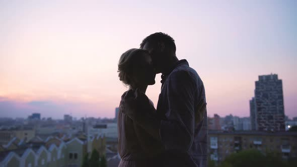 Thumbnail for Handsome Man Gently Kissing His Girl Warming Her from Evening Coolness, Sunset