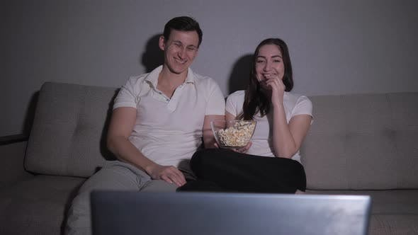 Happy Couple Watching a Movie on Tv Sitting on a Couch at Home