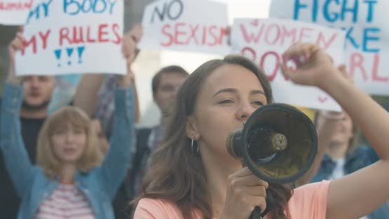 Young Beautiful Protest Leader Shouting Through Megaphone and Gesturing with People Shaking Feminism
