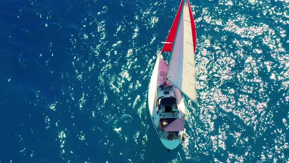 Thumbnail for Aerial View. Beautiful Sailing Yacht with a Red Sail Is Sailing on the Emerald Sea on a Sunny Day