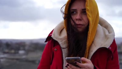 Portrait of Young Woman with Mobile Phone on Roof of Building