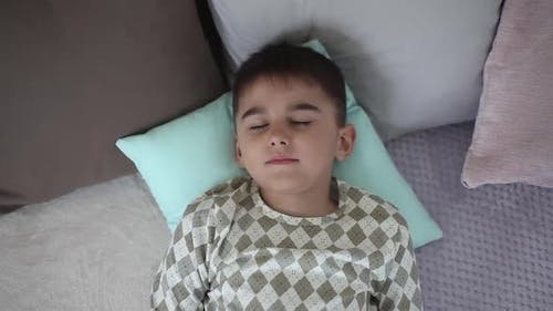 A Little Boy Wakes Up in the Morning on a Bed Having a Good Mood