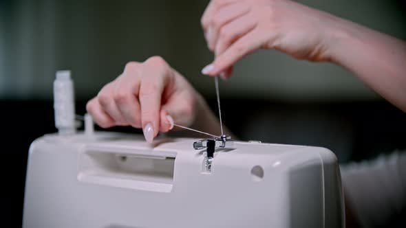 Thumbnail for Hand of Seamstress Sets a Skein of Thread on the Sewing Machine