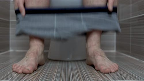 The Man Took Off Gray Panties While Sitting on the Toilet. A Man with Hairy Legs in the Toilet
