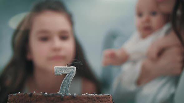 Thumbnail for Girl Blowing Candle on Birthday Cake at Family Party