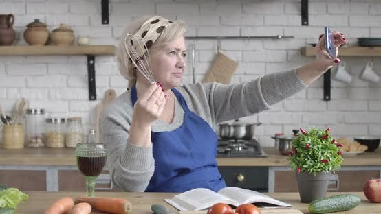 Thumbnail for Modern Senior Caucasian Woman Taking Selfies with Cooking Utility in the Kitchen. Portrait of