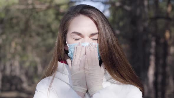 Thumbnail for Close-up of Young Brunette Woman in Protective Mask and Gloves Coughing in Sunny Spring Park