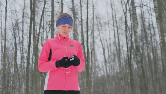 Thumbnail for A Young Woman on the Morning Jog Holds in Her Hands a Smartphone Picks a Music Track for Training