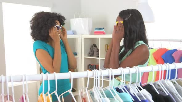 African American friends shopping and trying on sunglasses together