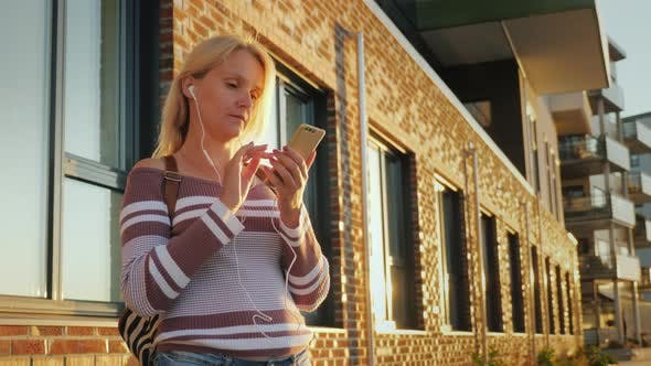 Thumbnail for A Young Woman Is Using the Application on a Smartphone, Standing By a Beautiful Brick Building at