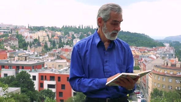 Thumbnail for Old Senior Man Man Reads Book - City (Buildings) in Background