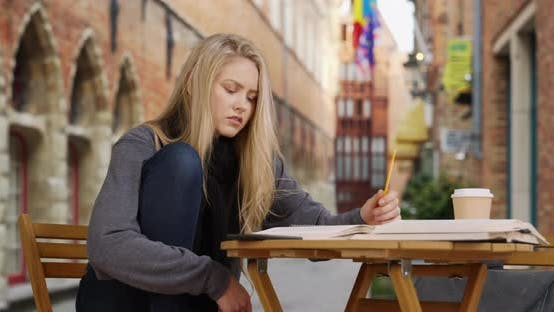 Thumbnail for White blonde woman studying in Bruges, Belgium has difficulty with school work