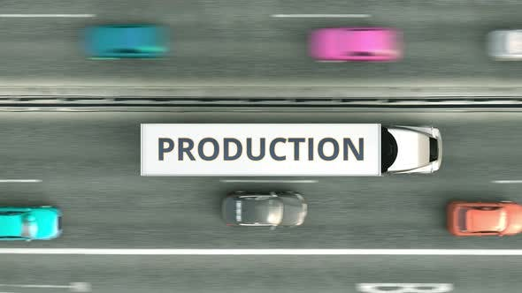 Trucks with PRODUCTION Text Driving Along the Road