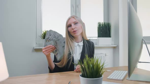 Relaxed Woman with Money in Office. Elegant Young Blond Female in Business Suit Sitting at Desk with
