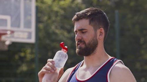 Nahaufnahme von jungen sportlichen Kerl Trinkwasser auf Outdoor Basketball Court