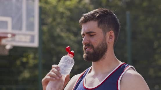 Thumbnail for Close Up of Young Sporty Guy Drinking Water at Outdoor Basketball Court