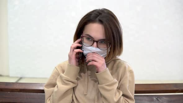 Thumbnail for A Young Woman in a Medical Mask Sits on a Bench in a Shopping Center and Talks on the Phone. The