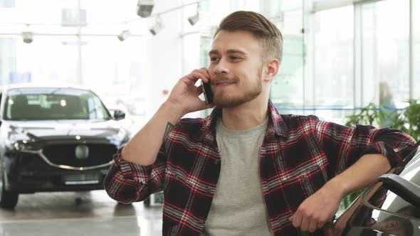 Thumbnail for Cheerful Handsome Man Talking on the Phone at the Car Dealership