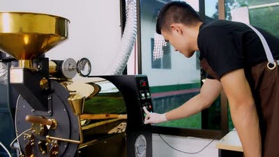 Asian Man Working With Roaster Machine