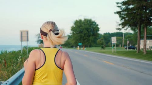 Middle-aged Woman Runs Along the Road in a Typical Suburb of the United States, a Healthy Lifestyle