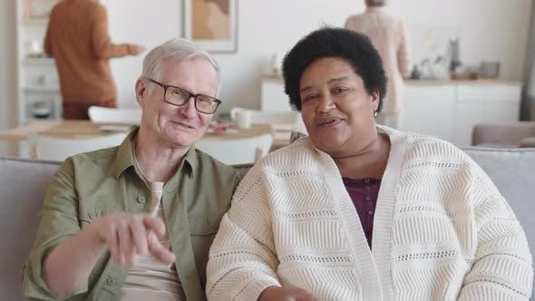 Multiethnic Senior Couple Watching TV Talking