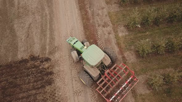 Cover Image for a Large Tractor Plows a Field