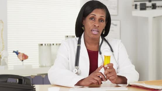 Thumbnail for Senior black woman doctor talking about medication bottle to camera