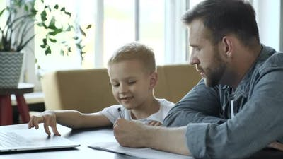 Supporting Son In His Studying. Side View Of Cheerful Young Father Helping His Son To Do Homework