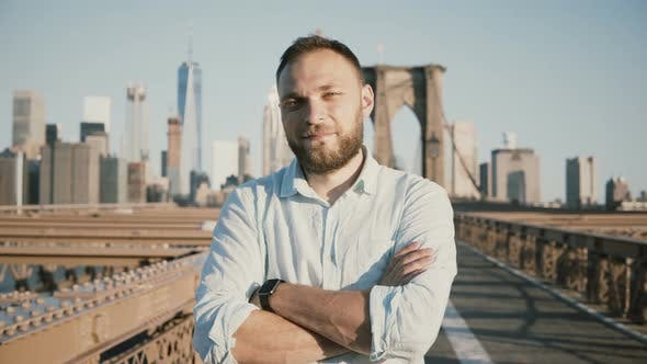 Thumbnail for junge positive männliche kaukasische businessman mit Armen gekreuzt Blick auf Kamera, Lächeln bei Brooklyn