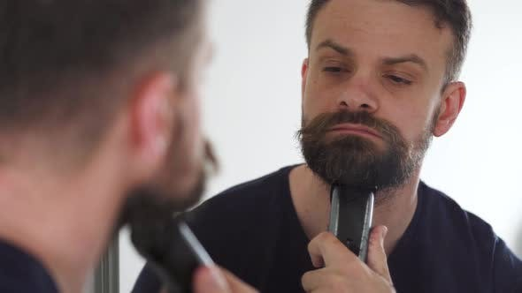 Thumbnail for Man Shaves His Beard Using an Electric Trimmer. Reflection in the Mirror
