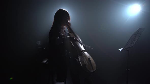 Thumbnail for Musician Girl in a Dark Room Rehearsing a Cello Playing and Rubbed Into a Music Stand. Silhouette