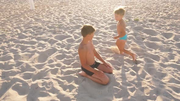 Happy Little Boy Running Around the White Sand Beach Is About a Teenage Brother in the Setting Sun