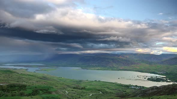 Thumbnail for Storm Clouds and Rain Approaching to Lake Geography Surrounded by Hilly Meadows