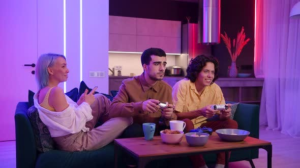 Thumbnail for Company of the Friends Enjoy Relaxing on Couch Playing Videogames and Having Fun in Modern Flat Lit