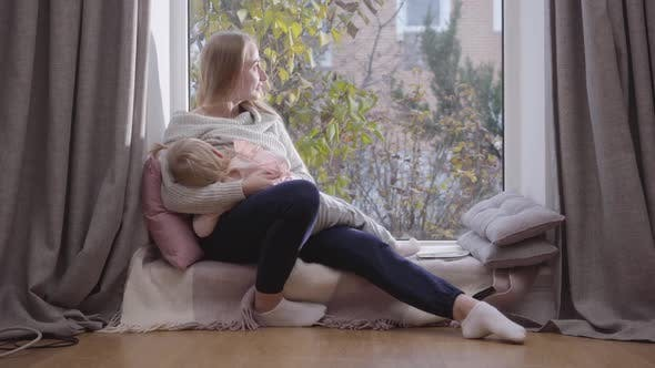 Thumbnail for Portrait of Young Happy Caucasian Woman Sitting on Low Windowsill and Holding Her Daughter on Hands