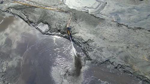 The Worker Washes Away the Soil with a Large Stream of Water