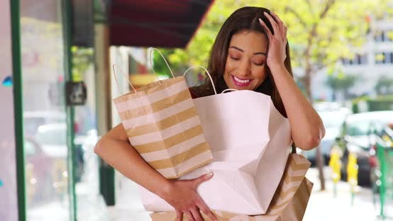 Thumbnail for Portrait of laughing shopaholic struggling to carry her purchases outside store